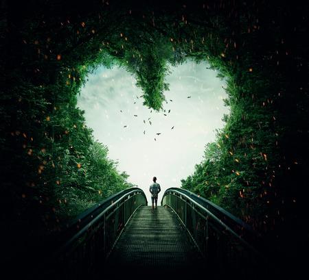Photo pour Boy walking on a bridge through the heart shape woods, following the light. Follow your heart concept - image libre de droit