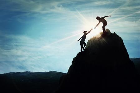 Foto de Silhouette of helping hand between two boys climbing a rocky dangerous cliff. Friendly hand on the high mountain hike. Inspirational teamwork, faith and support symbol. - Imagen libre de derechos