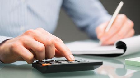 Foto de A female accountant uses a calculator and takes notes on a paper notebook on an office desk. - Imagen libre de derechos