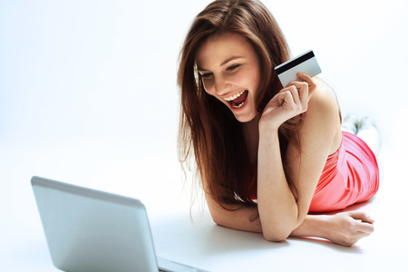 Photo pour A Happy Woman holding a credit card and shopping from the internet - image libre de droit