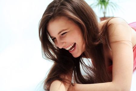 Foto de Happy woman laughing against white background - Imagen libre de derechos