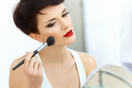 Photo pour Beauty Girl with Makeup Brush. Natural Make-up for Brunette Woman with Red Lips. Beautiful Face. Applying Makeup - image libre de droit