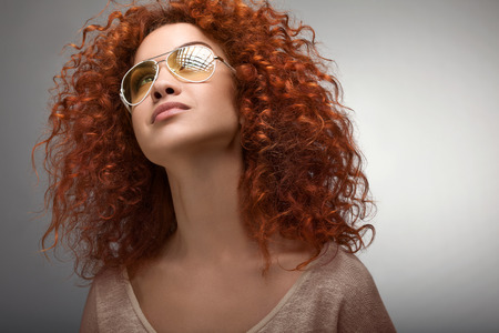 Photo pour Red Hair. Beautiful Woman with Curly Long Hair and Sunglases - image libre de droit