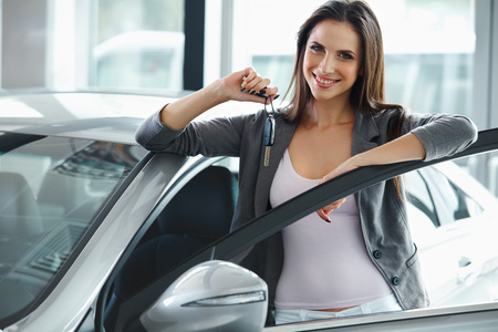 Photo pour Woman Driver Holding Car Keys. Car Showroom. - image libre de droit