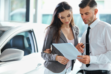 Foto de Young Woman Signing Documents at Car Dealership with Salesman - Imagen libre de derechos