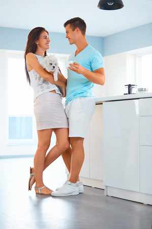 Young cheerful couple spending leisure time together with their dog in the kitchen at home