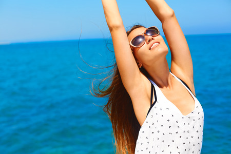 Photo pour Summer vacation. Happy woman enjoying the sun. She's wears white dress and dark sunglasses. She feels relaxed, happy, healthy and free. - image libre de droit