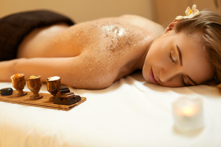 Foto de Body Scrub. Beautiful Blonde Gets a Salt Scrub Beauty Treatment in the spa Salon - Imagen libre de derechos