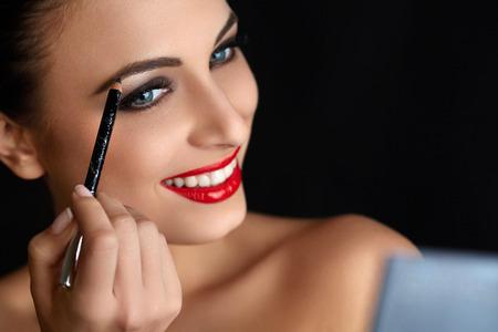 Make-up. Beautiful Woman Doing Makeup. Eyebrow Pencil. Red Lips
