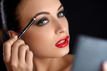 Foto de Make-up. Beautiful Woman Doing Makeup Eyebrow Pencil. Red Lips - Imagen libre de derechos