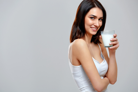 Happy young woman drinking milk