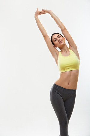 Photo for Woman doing stretching exercises against white - Royalty Free Image