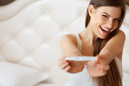 Foto de Happy Woman With Pregnancy Test - Imagen libre de derechos