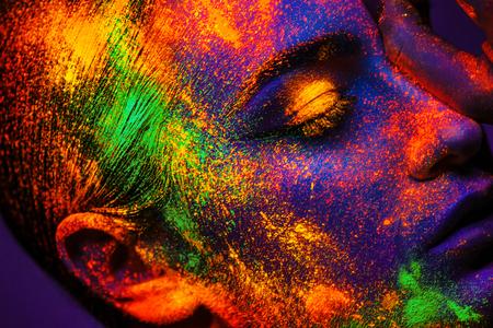 Photo pour Portrait of sexy adult girl with neon makeup powder on face in studio - image libre de droit