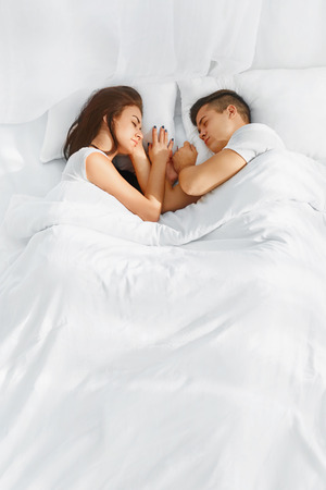 Photo pour Portrait of young lovely couple sleeping in the bed on white blankets faced to each other - image libre de droit