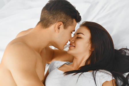 Foto de Close up portrait of a young romantic couple hugging and kissing, laying down on a white bed and loving each other. Love and relationships lifestyle, interior bedroom. - Imagen libre de derechos