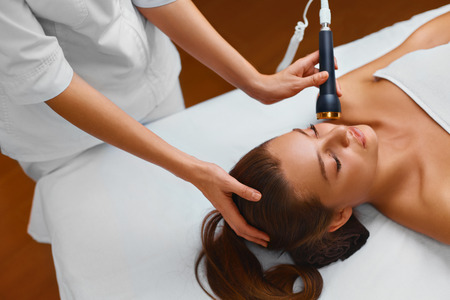 Photo pour Face Skin Care. Beautiful Young Healthy Caucasian Woman Lies On A Table In A Medical Beauty Cosmetology Spa Salon Getting Facial Skin Care Treatment. Ultrasound Cavitation Anti-aging, Rejuvenation, Lifting Procedure. Beautician Applying Regenerative, Mois - image libre de droit