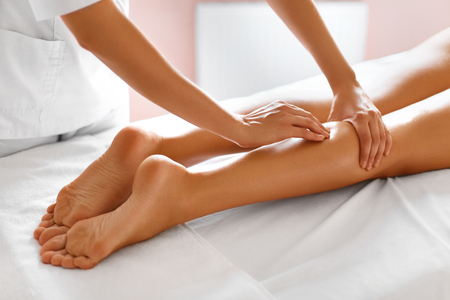 Foto de Spa Woman. Close-up Of Sexy Woman Getting Spa Treatment. Leg Massage Therapy In Spa Salon. Masseur Applying Moisturizing Oil And Massaging Beautiful Long Tanned Female Legs. Body Care, Skin Care, Wellbeing, Wellness Concept. - Imagen libre de derechos