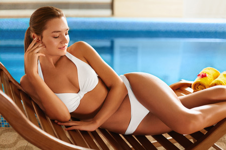 Foto de Body Care. Attractive Sexy Healthy Young Caucasian Woman With Perfect Tanned Slim Body And Dark Beautiful Hair In White Bikini Lying On The Deckchair By Swimming Pool In Resort Spa Hotel. Spa, Sauna, Skin Care, Lifestyle, Wellness, Wellbeing Concept. - Imagen libre de derechos