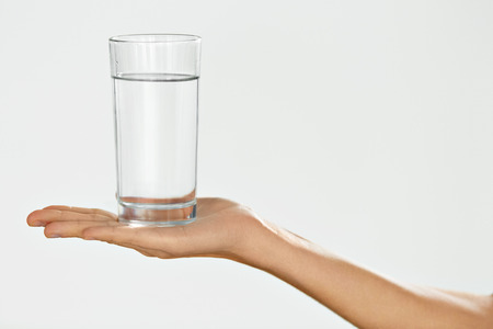 Photo pour Water Glass. Health And Diet Concept. Woman's Hand Holding Glass. Healthy Eating, Lifestyle. Drinks. Healthcare And Beauty. Hydration - image libre de droit