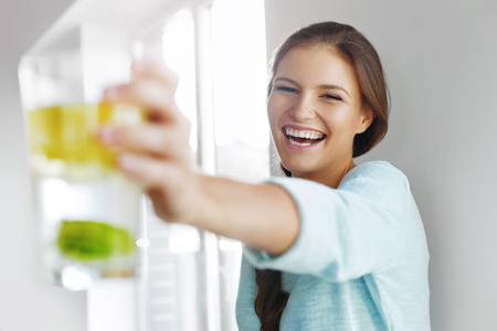 Foto de Healthy Lifestyle Concept, Diet And Fitness. Smiling Woman Drinking Refreshing Water With Fresh Organic Lemon , Lime, Mint. Detox Vitamin-fortified Water. Healthy Eating, Food. Vitamin, Diet Concept. - Imagen libre de derechos
