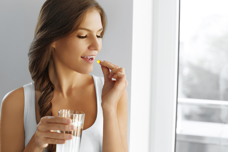 Photo pour Diet. Nutrition. Vitamins. Healthy Eating, Lifestyle. Close Up Of Happy Smiling Woman Taking Pill With Cod Liver Oil Omega-3 And Holding A Glass Of Fresh Water In Morning. Vitamin D, E, A Fish Oil Capsules. - image libre de droit