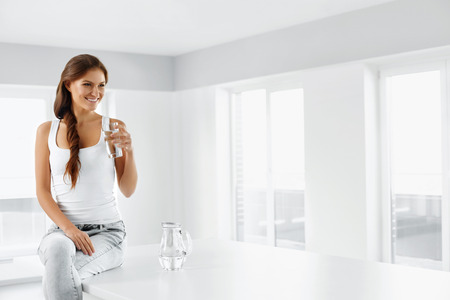 Foto de Healthy Lifestyle. Close-up Portrait Of Happy Smiling Young Woman With Glass Of Refreshing Cold Water. Healthy Eating. Diet. Dieting Concept.  Nutrition. Healthcare And Beauty. - Imagen libre de derechos