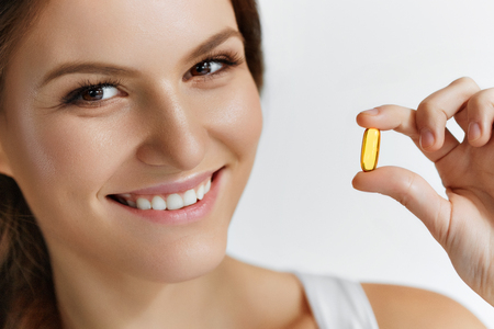 Photo pour Vitamins. Healthy Eating. Close Up Of Happy Beautiful Girl With Pill With Cod Liver Oil Omega-3. Nutrition. Healthy Lifestyle. Nutritional Supplements. Sport, Diet Concept. Vitamin D, E, A Fish Oil Capsules. - image libre de droit