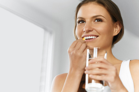 Foto per Vitamins. Healthy Diet, Eating, Lifestyle. Happy Smiling Woman Taking Pill With Cod Liver Oil Omega-3 And Holding A Glass Of Fresh Water. Healthcare And Beauty. Vitamin D, E, A Fish Oil Capsules. Nutrition. - Immagine Royalty Free