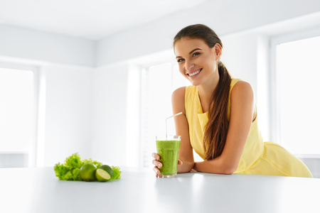 Photo for Healthy Meal. Happy Beautiful Smiling Woman Drinking Green Detox Vegetable Smoothie. Healthy Lifestyle, Food And Eating. Drink Juice. Diet, Health And Beauty Concept. - Royalty Free Image