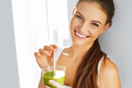 Photo pour Healthy Food Eating. Happy Beautiful Smiling Woman Drinking Green Detox Vegetable Smoothie. Diet. Healthy Lifestyle, Vegetarian Meal. Drink Juice. Health Care And Beauty Concept. - image libre de droit