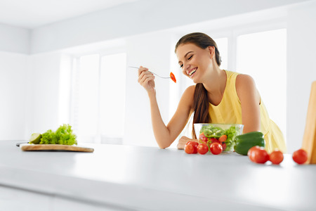 Photo pour Healthy Diet. Beautiful Smiling Woman Eating Fresh Organic Vegetarian Salad In Modern Kitchen. Healthy Eating, Food And Lifestyle Concept. Health, Beauty, Dieting Concept. - image libre de droit