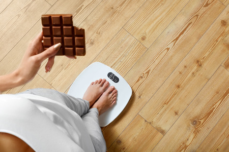 Foto de Diet. Young Woman Standing On Weighing Scale And Holding Chocolate Bar. Sweets Are Unhealthy Junk Food. Sugar Is Bad For Health. Dieting, Healthy Eating, Lifestyle. Weight Loss. Top View - Imagen libre de derechos