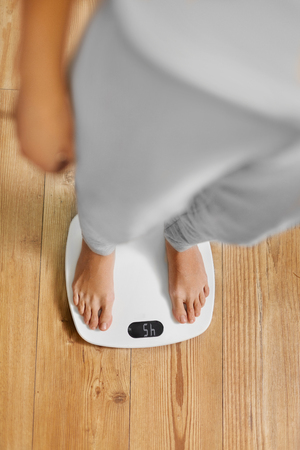 Foto de Diet. Top View Of Female Bare Feet Standing On A Scale. Caucasian Young Woman Measuring Body Weight On Weighing Scale At Home. Weight Loss. Dieting; Exercising. Healthy Eating; Lifestyle. - Imagen libre de derechos