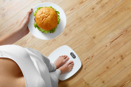 Foto de Diet And Fast Food Concept. Overweight Woman Standing On Weighing Scale Holding Burger Hamburger. Unhealthy Junk Food. Dieting, Lifestyle. Weight Loss. Obesity. Top View - Imagen libre de derechos