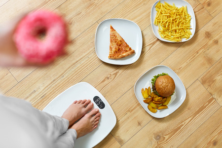 Photo pour Diet And Fast Food Concept. Overweight Woman Standing On Weighing Scale Holding Donuts. French Fries, Hamburger And Pizza. Unhealthy Junk Food. Dieting, Lifestyle. Weight Loss. Obesity. Top View - image libre de droit