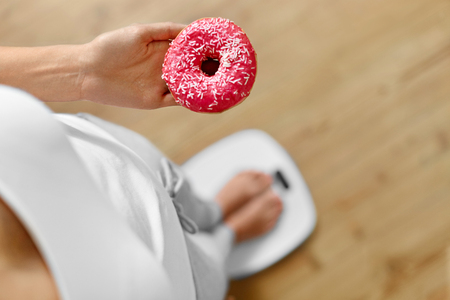 Foto de Diet Concept. Young Woman Measuring Body Weight On Weighing Scale While Holding Glazed Donut With Sprinkles. Sweets Are Unhealthy Junk Food. Dieting, Healthy Eating, Lifestyle. Weight Loss. Top View - Imagen libre de derechos
