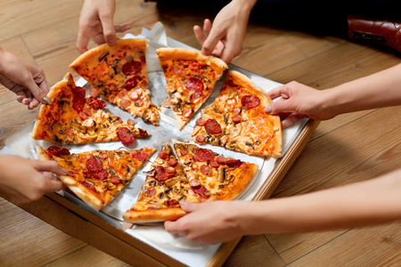 Foto de Eating Pizza. Group Of Friends Sharing Pizza Together. People Hands Taking Slices Of Pepperoni Pizza.  Fast Food, Friendship, Leisure, Lifestyle. - Imagen libre de derechos