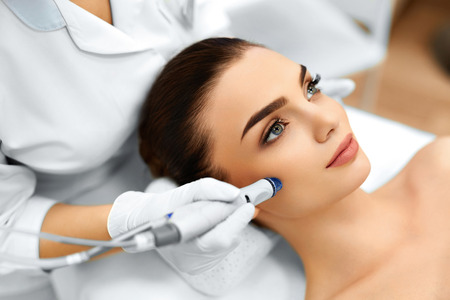 Photo pour Face Skin Care. Close-up Of Woman Getting Facial Hydro Microdermabrasion Peeling Treatment At Cosmetic Beauty Spa Clinic. Hydra Vacuum Cleaner. Exfoliation, Rejuvenation And Hydratation. Cosmetology. - image libre de droit