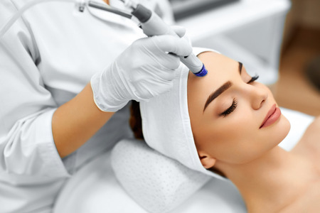 Photo for Face Skin Care. Close-up Of Woman Getting Facial Hydro Microdermabrasion Peeling Treatment At Cosmetic Beauty Spa Clinic. Hydra Vacuum Cleaner. Exfoliation, Rejuvenation And Hydratation. Cosmetology. - Royalty Free Image