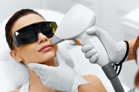 Photo for Face Care. Facial Laser Hair Removal. Beautician Giving Laser Epilation Treatment To Young Woman's Face At Beauty Clinic. Body Care. Hairless Smooth And Soft Skin. Health And Beauty Concept. - Royalty Free Image