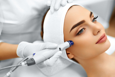 Foto de Face Skin Care. Close-up Of Woman Getting Facial Hydro Microdermabrasion Peeling Treatment At Cosmetic Beauty Spa Clinic. Hydra Vacuum Cleaner. Exfoliation, Rejuvenation And Hydratation. Cosmetology. - Imagen libre de derechos
