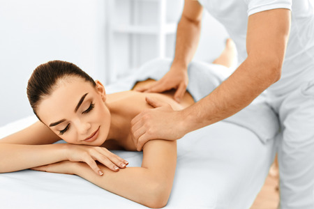 Photo pour Spa Woman. Beauty Treatment. Beautiful Young Healthy Caucasian Girl Relaxing With Hand Massage Procedure In The Spa Salon. Masseur Massaging Her Back. Body Care. Skin Care, Wellness, Wellbeing. - image libre de droit