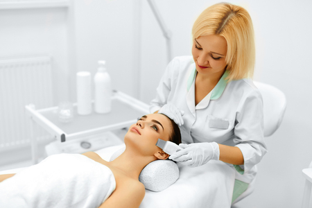 Foto de Skin Care. Close-up Of Beautiful Woman Receiving Ultrasound Cavitation Facial Peeling. Ultrasonic Skin Cleansing Procedure. Beauty Treatment. Cosmetology. Beauty Spa Salon. - Imagen libre de derechos