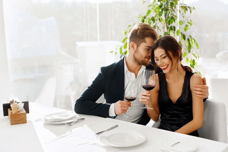 Photo pour Love. Happy Romantic Smiling Couple Having Dinner, Embracing, Drinking Wine, Celebrating Holiday, Anniversary Or Valentine's Day In Gourmet Restaurant. Romance, Relationships Concept. Celebration - image libre de droit