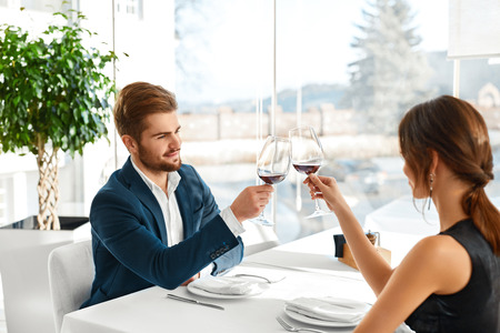 Foto de Celebration. Happy Romantic Couple In Love Cheering With Glasses Of Red Wine, Having Dinner In Luxury Gourmet Restaurant, Celebrating Anniversary Or Valentine's Day. Romance, Relationship. Cheers - Imagen libre de derechos