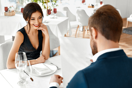 Photo pour Romantic Couple In Love Having Dinner In Luxury Gourmet Restaurant. Happy Beautiful Lovely People Reading Menu, Choosing Food, Celebrating Anniversary Or Valentine's Day. Romance And Relationships. - image libre de droit