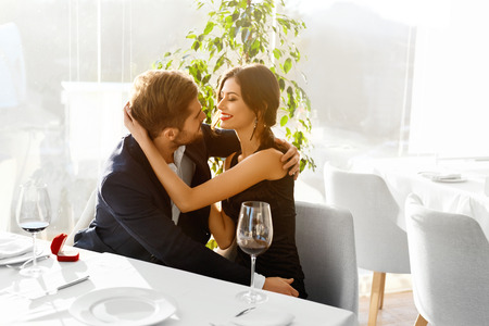 Photo pour Relationships. Romantic Couple In Love Decided To Get Married. Closeup Of Man Is Going To Propose Marriage To Woman With Engagement Diamond Ring In Luxury Gourmet Restaurant. Wedding, Romance Concept. - image libre de droit