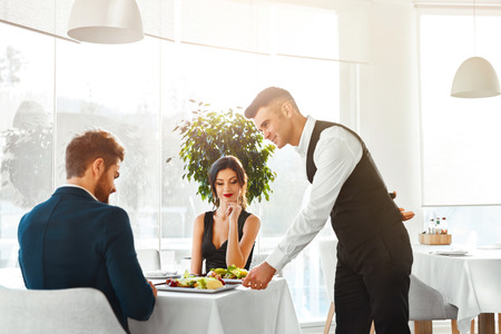 Photo pour Happy Couple In Love Having Romantic Dinner In Luxury Gourmet Restaurant. Waiter Serving Meal. People Celebrating Anniversary Or Valentine's Day. Romance, Relationship Concept. Healthy Food Eating. - image libre de droit