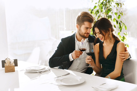 Foto de Love. Happy Romantic Smiling Couple Having Dinner, Embracing, Drinking Wine, Celebrating Holiday, Anniversary Or Valentine's Day In Gourmet Restaurant. Romance, Relationships Concept. Celebration - Imagen libre de derechos